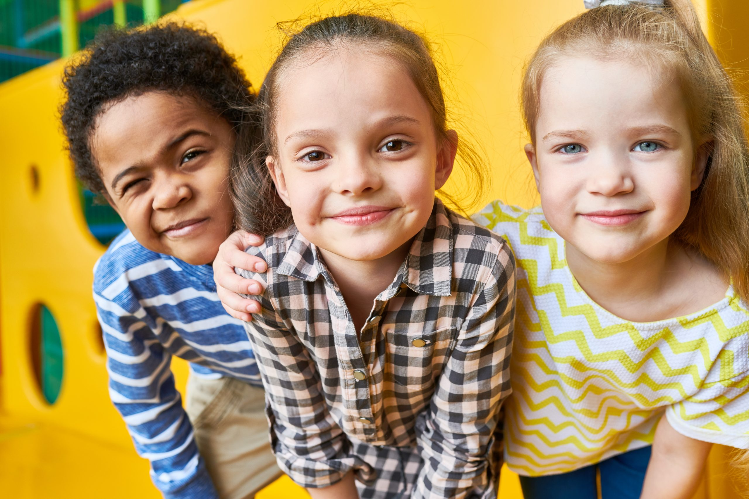 Colorful portrait of three happy kids posing looking at camera while having fun playing in children center